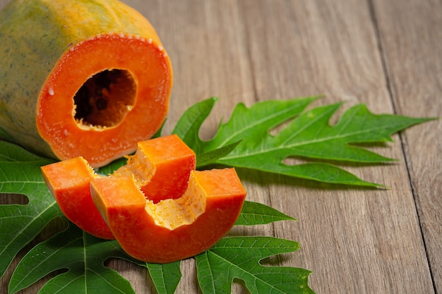 Fresh papaya, cut into pieces, put on a wooden floor