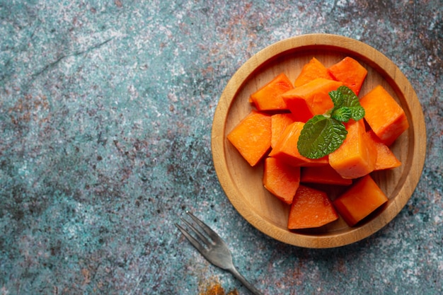Fresh papaya, cut into pieces, put on a wooden plate.