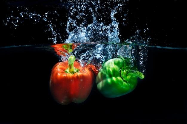 Fresh paprika chilies splashing into clear water splash