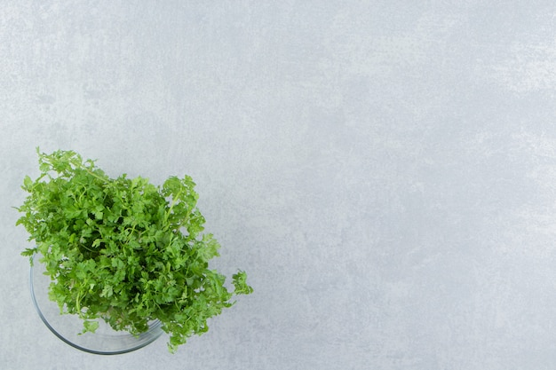 A fresh parsley in the glass , on the marble background.