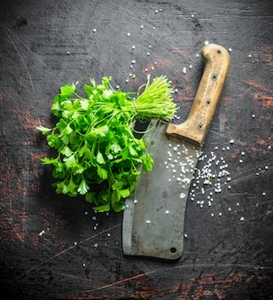 Fresh parsley with big knife. on dark rustic background