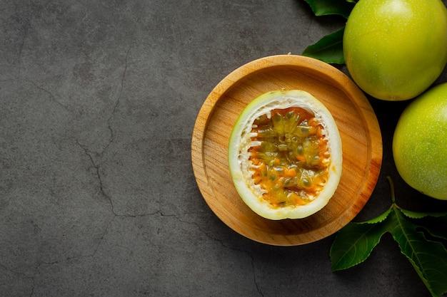 Frutto della passione fresco tagliato a metà posto sul piatto di legno