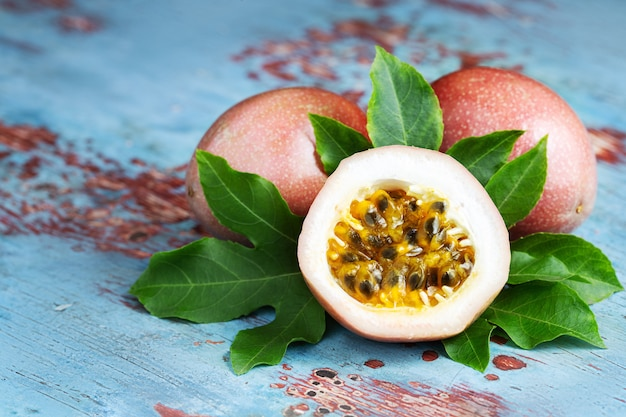 Fresh passion fruit with original leaves on blue wooden background
