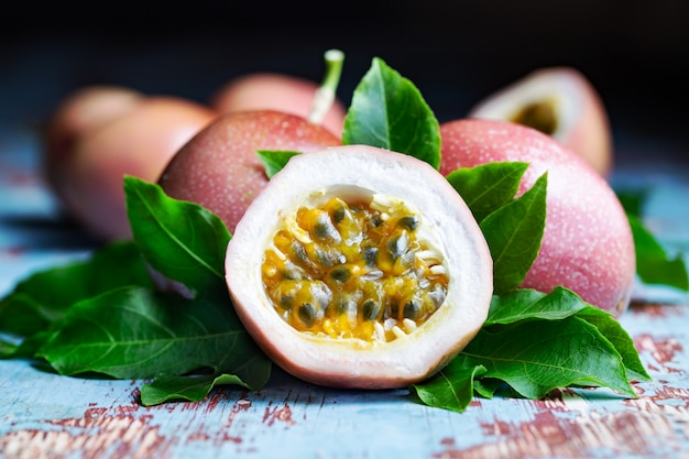 Fresh passion fruit with original leaves on blue wooden table