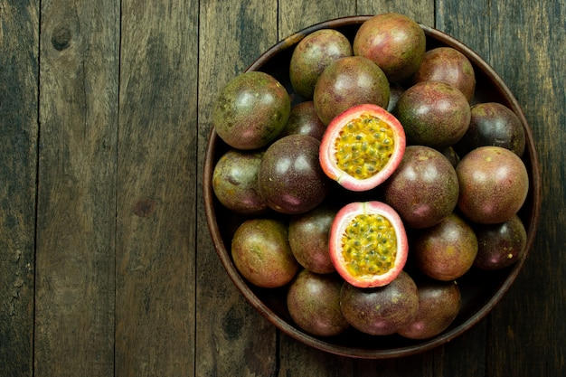 Fresh passion fruit in wood bowl on table copyspace