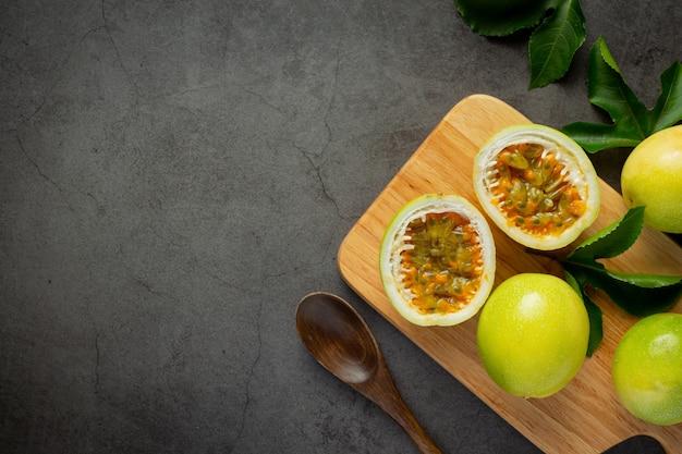 Свежие фрукты маракуйи разрезать пополам на деревянной разделочной доске