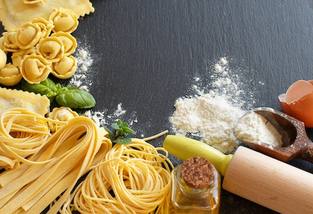 Свежая паста и ингредиенты на темной доске крупным планом