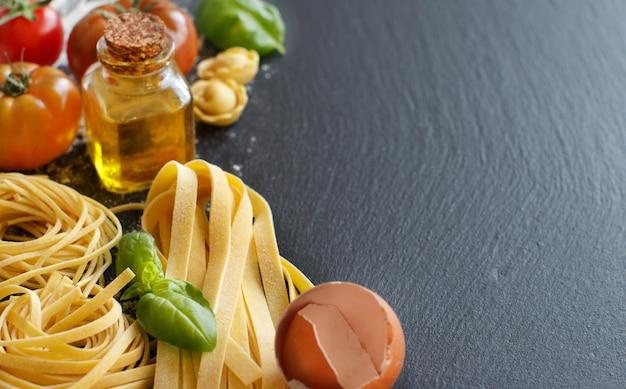 Свежая паста и ингредиенты на темной доске