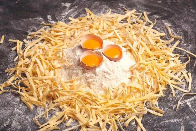 新鮮なパスタの背景木製の背景に新鮮な卵と小麦粉を使って家庭の台所で調理された自家製イタリアンフェットチーネパスタイタリア料理と料理のコンセプト高品質の写真