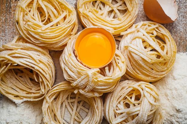 生パスタ。卵と小麦粉で飾られた素朴なスタイルの木製のテーブルで調理された自家製イタリアンパスタ。
