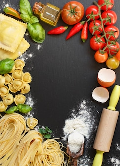 Fresh pasta and ingredients on a dark board top view with copy space
