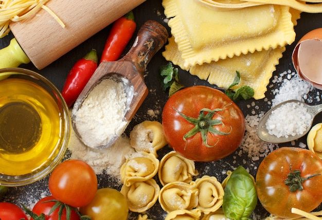Fresh pasta and ingredients on a dark board