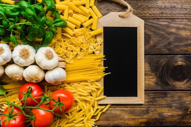 Fresh pasta ingredients near blackboard Free Photo