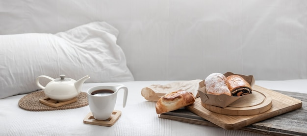 白いベッドの背景に焼きたてのペストリーと一杯のコーヒー。ブランチと週末のコンセプト。