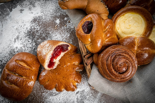 Fresh pastries buns in the basket in rustic style bakery with eggs and gluten on wooden table