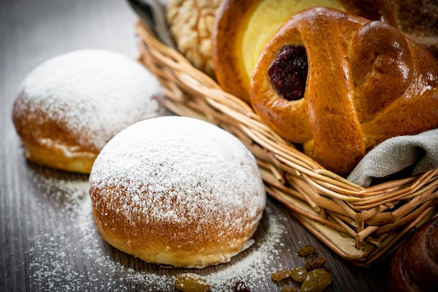 Fresh pastries buns in the basket in rustic style bakery with white wheat on wooden table