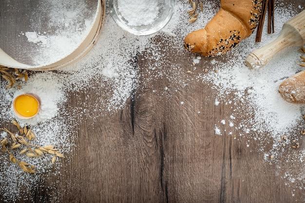 木製のテーブルに卵とグルテンを入れた素朴なスタイルのベーカリーのバスケットに焼きたてのペストリーパン