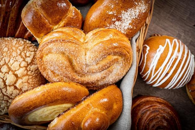 木製のテーブルに白い小麦と素朴なスタイルのパン屋のバスケットに焼きたてのペストリーパン