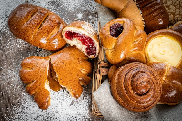 Fresh pastries buns in rustic style bakery on wooden table
