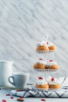 Fresh pastries on cake stand with cup and nut food over concrete surface