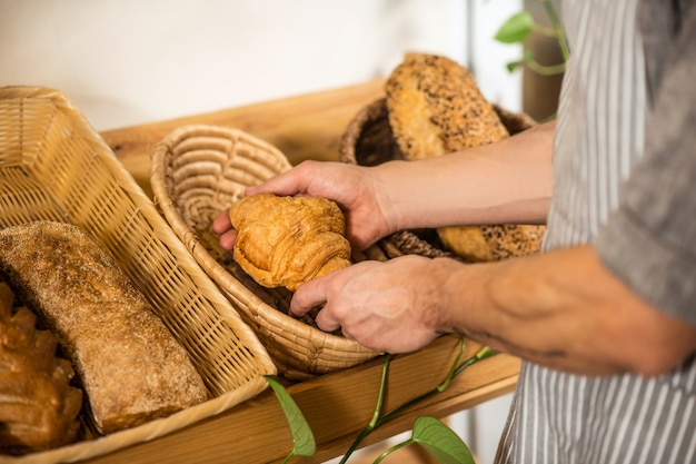 Fresh pastries, croissant. caring hands of man carefully placing bakery products in baskets in store, face is not visible