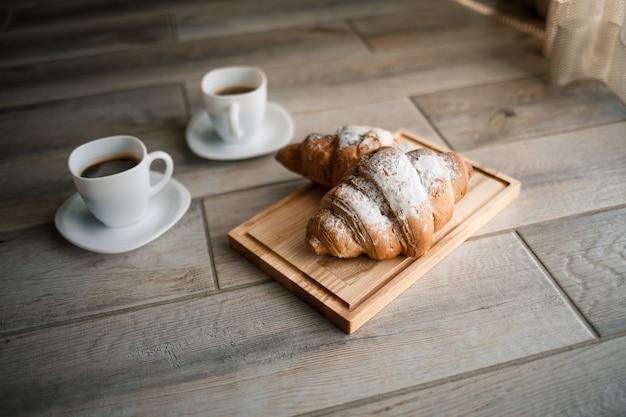 木の板にチョコレートとブラックコーヒー2杯の焼きたてのペストリークロワッサン。ロマンチックな朝食