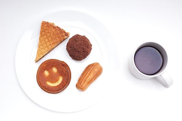 Свежая выпечка на белой тарелке и чашка кофе, изолированные на белом фоне