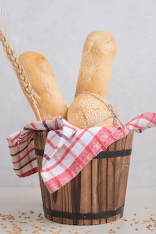 Fresh pastry of bread on wooden basket with tablecloth. high quality photo