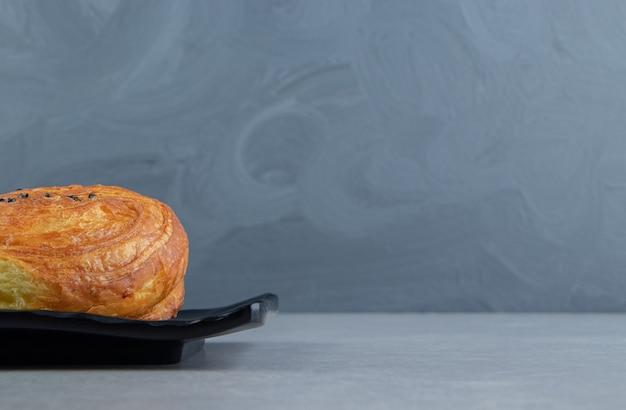Гогаль свежего теста на черной тарелке.