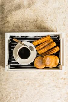 Fresh pastry near coffee on tray