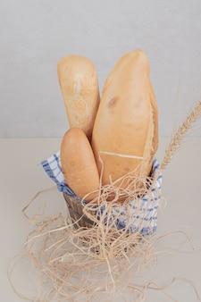 テーブルクロスと木製のバスケットにパンの焼きたてのペストリー