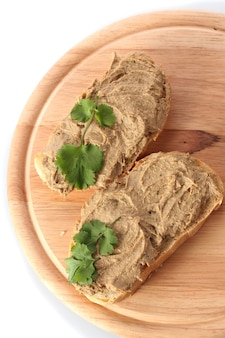 Fresh pate on bread on wooden board