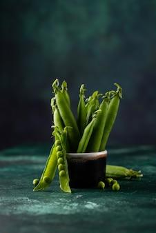 緑のテーブルの上の新鮮なエンドウ豆の鞘