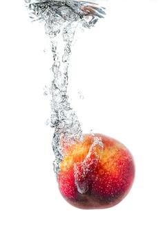 Fresh peach falling in water