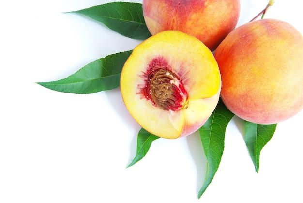 白で隔離される緑の葉を持つ新鮮な桃の果実