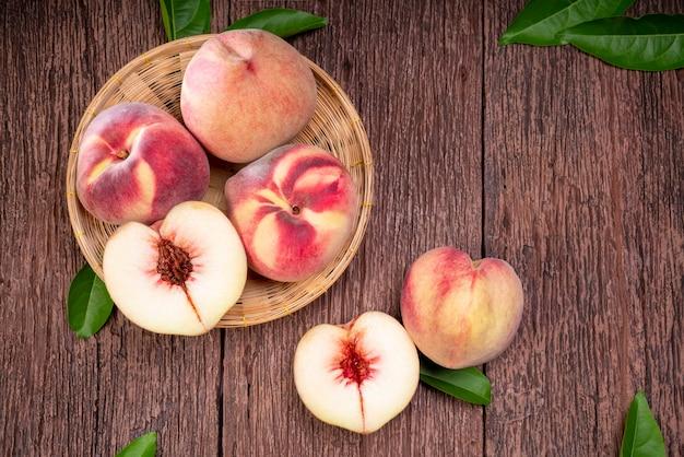 나무 접시에 잎을 가진 신선한 복숭아 과일 나무 대나무 배경에 나무 접시에 복숭아