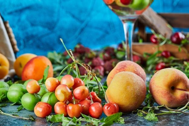 Pesche fresche, ciliegie, fette di limone e menta sulla superficie in marmo
