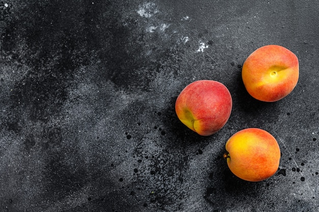 Fresh peaches fruits on dark wooden background.  top view. copy space.