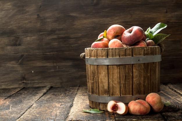 Свежие персики в деревянном ведре на деревянном фоне