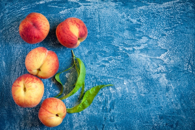 Свежие персики на синем каменном столе