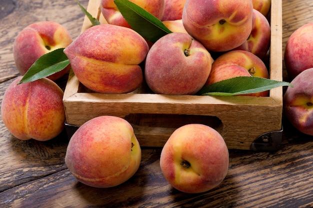 Свежие персики с листьями в деревянном ящике Premium Фотографии
