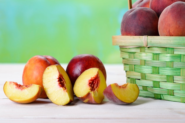 Fresh peaches on a wooden table next to the basket