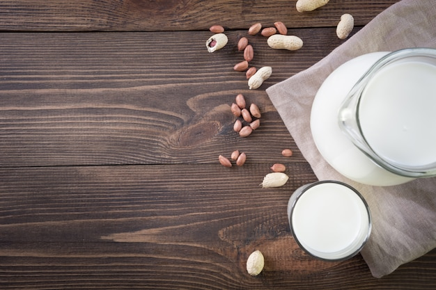Fresh peanut milk in glass and pitcher on dark wooden table background. rustic style.