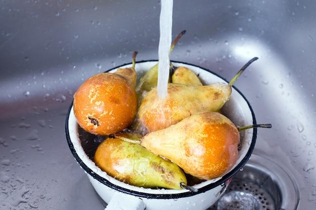 Свежая груша моется на дуршлаге в раковине.
