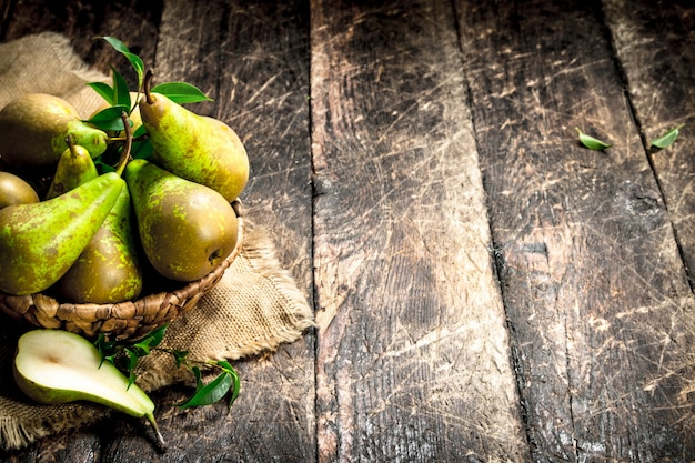 Fresh pears in a basket on wooden table.