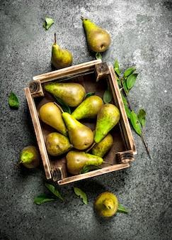 箱に入った新鮮な梨。素朴な背景に。