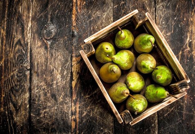 箱に入った新鮮な梨。木製の背景に。