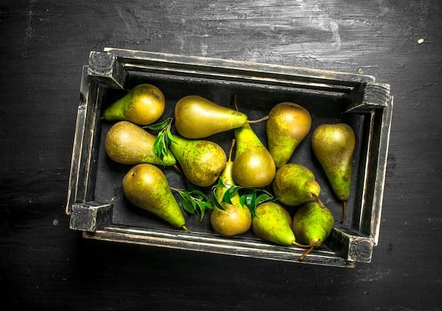 箱に入った新鮮な梨。黒い黒板に。