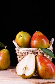 木製のテーブルの上のバスケットに葉を持つ新鮮な梨