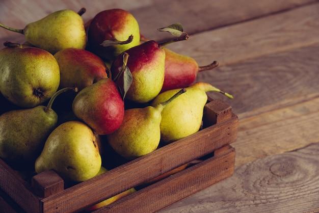 Свежие груши с листьями в деревянном ящике на деревянном фоне.